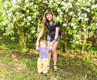 Happy woman and child in the blooming spring garden.  Mothers day holiday concept Royalty Free Stock Images