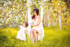 Happy woman and child in the blooming spring garden.Mothers day. Happy women and child in the blooming spring garden.Mothers day holiday concept Royalty Free Stock Photos