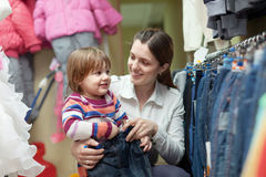 Happy woman and child chooses jeans Stock Photography
