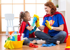 Happy woman with child cleaning room and having fun playing at home. Family housework conception. Royalty Free Stock Photo