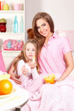 Happy woman and child eating fruit Stock Photos