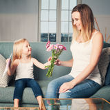 Happy Woman and Child Girl with Flowers at Home. Loving Daughter and Mother stock images