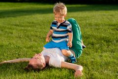Happy woman and child having fun outdoor on meadow Royalty Free Stock Images
