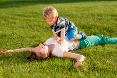 Happy woman and child having fun outdoor on meadow Stock Photos
