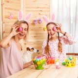 Happy woman with child paint easter eggs Stock Photos