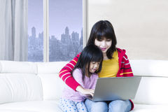 Happy woman and child playing laptop Stock Photos