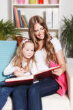 Happy woman and child reading a book Stock Photography