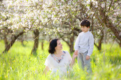 Happy woman and child in spring apple garden Royalty Free Stock Photos