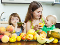 Happy woman with children eating fruits royalty free stock photos