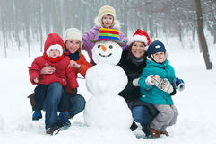 Happy woman with children snowman in winter Royalty Free Stock Images