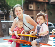 Happy woman with children on swings Stock Photo