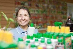 Happy  woman chooses liquid fertilizer Stock Photos