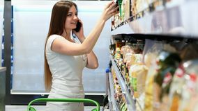 Happy woman chooses products in the Supermarket and talking on a mobile phone, customer selects goods on the shelves in stock footage