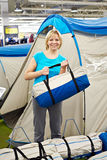 Happy woman chooses tent camp in store leisure goods Stock Photos