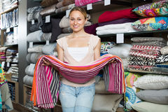 Happy woman choosing blanket. In bedding section in shop Stock Photo