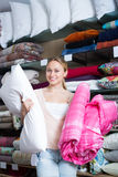 Happy woman choosing blanket and pillow. Portrait of happy woman choosing blanket, pillow and textile in bedding section in shop Royalty Free Stock Photography