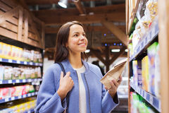 Happy woman choosing and buying food in market. Sale, shopping, consumerism and people concept - happy young woman choosing and buying food in market Royalty Free Stock Images