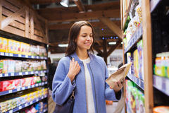 Happy woman choosing and buying food in market Royalty Free Stock Photo