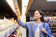 Happy woman choosing and buying food in market Stock Image