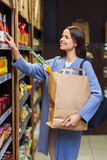 Happy woman choosing and buying food in market Stock Images