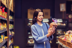 Happy woman choosing and buying food in market. Sale, shopping, consumerism and people concept - happy young woman choosing and reading label on bread in market Royalty Free Stock Image