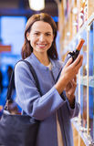 Happy woman choosing and buying wine in market royalty free stock image