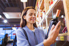 Happy woman choosing and buying wine in market Stock Photos