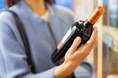 Happy woman choosing and buying wine in market Royalty Free Stock Photo
