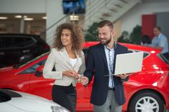 Happy woman choosing car with manager of car dealership. royalty free stock photos