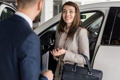 Happy Woman Choosing Car in Showroom. Portrait of beautiful modern women smiling happily while listening to car salesman choosing luxury car in showroom Stock Photo