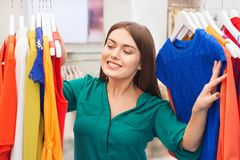 Happy woman choosing clothes at clothing store stock photos