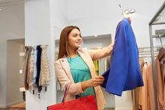 Happy woman choosing clothes at clothing store stock images