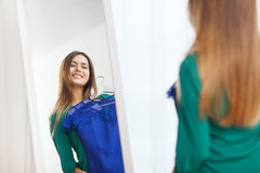 Happy woman choosing clothes at home wardrobe. Clothing, fashion, style and people concept - happy woman choosing clothes at home wardrobe Royalty Free Stock Photo