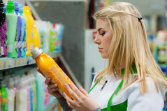Happy woman choosing detergent in laundry section of supermarket Royalty Free Stock Photo