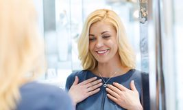 Happy woman choosing pendant at jewelry store Stock Image