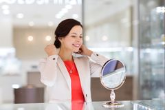Happy woman choosing pendant at jewelry store Royalty Free Stock Image