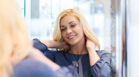 Happy woman choosing pendant at jewelry store Stock Images
