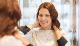 Happy woman choosing pendant at jewelry store Royalty Free Stock Photos