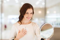 Happy woman choosing pendant at jewelry store Royalty Free Stock Photo