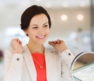 Happy woman choosing pendant at jewelry store. Sale, consumerism, shopping and people concept - happy woman choosing and trying on pendant at jewelry store Royalty Free Stock Image