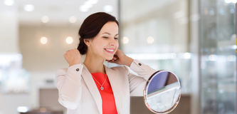 Happy woman choosing pendant at jewelry store. Sale, consumerism, shopping and people concept - happy woman choosing and trying on pendant at jewelry store Stock Images