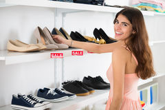 Happy Woman Choosing Shoes From Shelf In Store Stock Photos