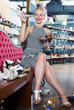 Happy woman choosing two pairs of new shoes Stock Photo