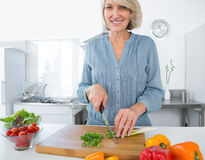 Happy woman chopping vegetables. At the kitchen counter Stock Photo