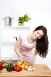 Happy woman chopping yellow paprika. Happy woman in a kitchen cutting yellow paprika for salad Royalty Free Stock Photos
