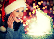 Happy woman in a Christmas cap opens the magic box Stock Photo