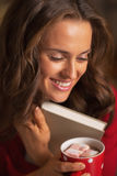 Happy woman with christmas cup of hot chocolate hugging book Stock Photo