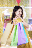 Happy woman with christmas gift in mall. Attractive young woman carrying christmas gift with shopping bags in the shopping center Stock Photos