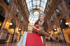 Happy woman with Christmas gift and shopping bags in Milan Stock Image