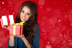 Happy woman with christmas gifts. red background. Stock Images